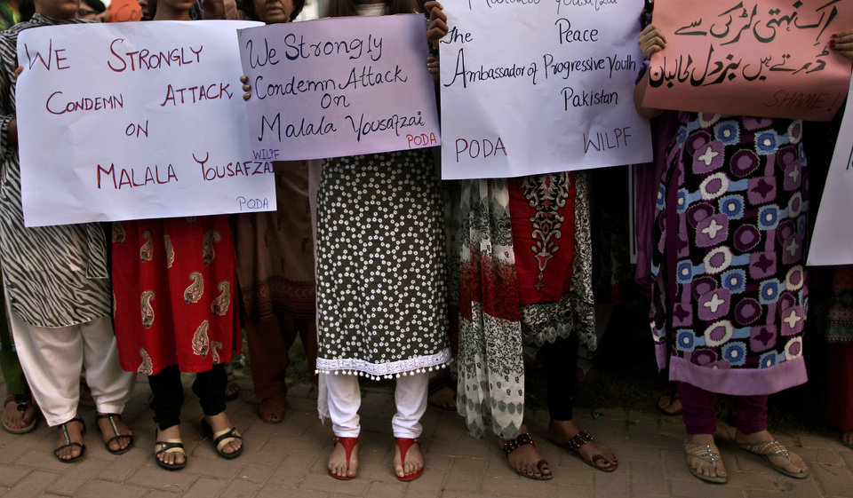 Photo -   Pakistani women, hold banners during a protest condemning the attack on schoolgirl Malala Yousufzai, in Islamabad, Pakistan, Wednesday, Oct. 10, 2012. Pakistani doctors successfully removed a bullet Wednesday from the neck of a 14-year-old girl who was shot by the Taliban for speaking out in support of education for women, a government minister said. Banner top right reads,