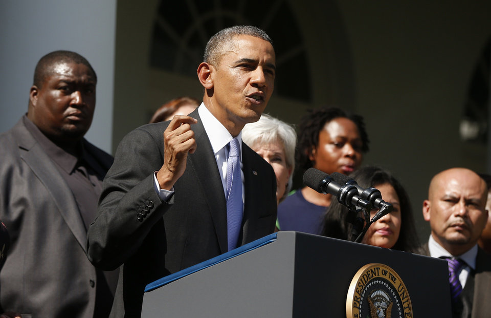Photo - President Barack Obama stands with people who support the Affordable Care Act, his signature health care law, as he speaks in the Rose Garden of the White House in Washington, Tuesday, Oct. 1, 2013. Congress plunged the nation into a partial government shutdown Tuesday as a long-running dispute over President Barack Obama's health care law forced about 800,000 federal workers off the job, suspending all but essential services. (AP Photo/Charles Dharapak)