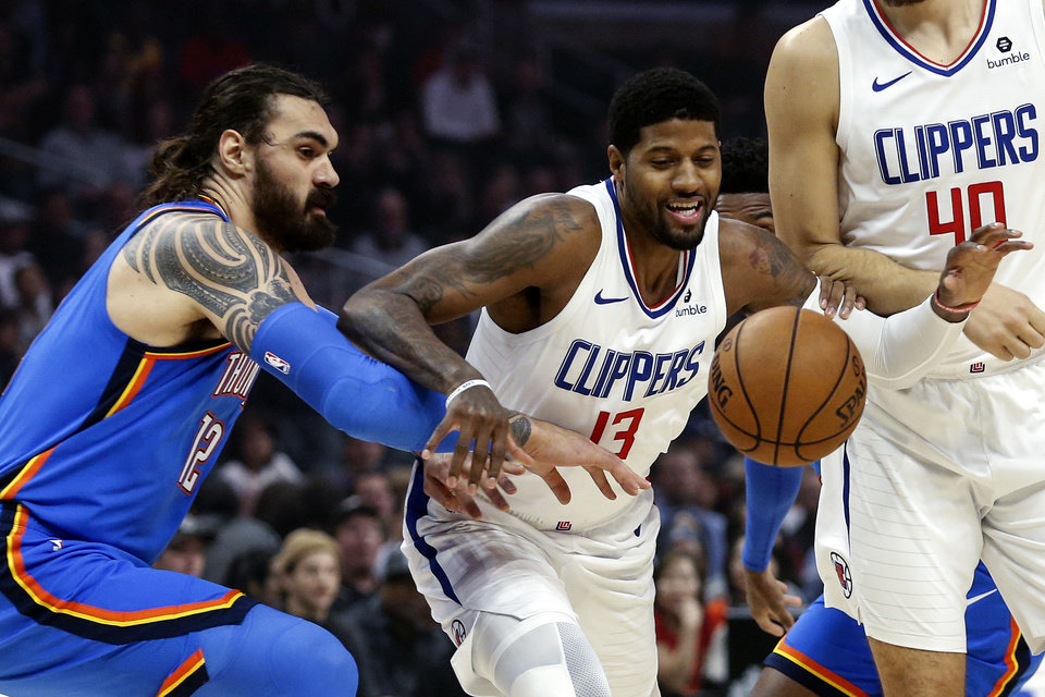 Photo - Los Angeles Clippers' Paul George (13) and Oklahoma City Thunder's Steven Adams (12) fight for a ball during the first half of an NBA basketball game, Monday, Nov. 18, 2019, in Los Angeles. (AP Photo/Ringo H.W. Chiu)