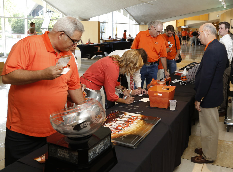 Photo - Fans line up for OSU swag during the OSU Cowboy Caravan at the National Cowboy and Western Heritage Museum Tuesday, August 5, 2014. Photo by Doug Hoke, The Oklahoman