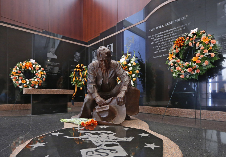 Photo - Flowers are displayed at the memorial to the 10 men killed in the Jan. 27, 2001 Oklahoma State plane crash before the start of an NCAA college basketball game between West Virginia and Oklahoma State in Stillwater, Okla., Saturday, Jan. 25, 2014. (AP Photo/Sue Ogrocki)
