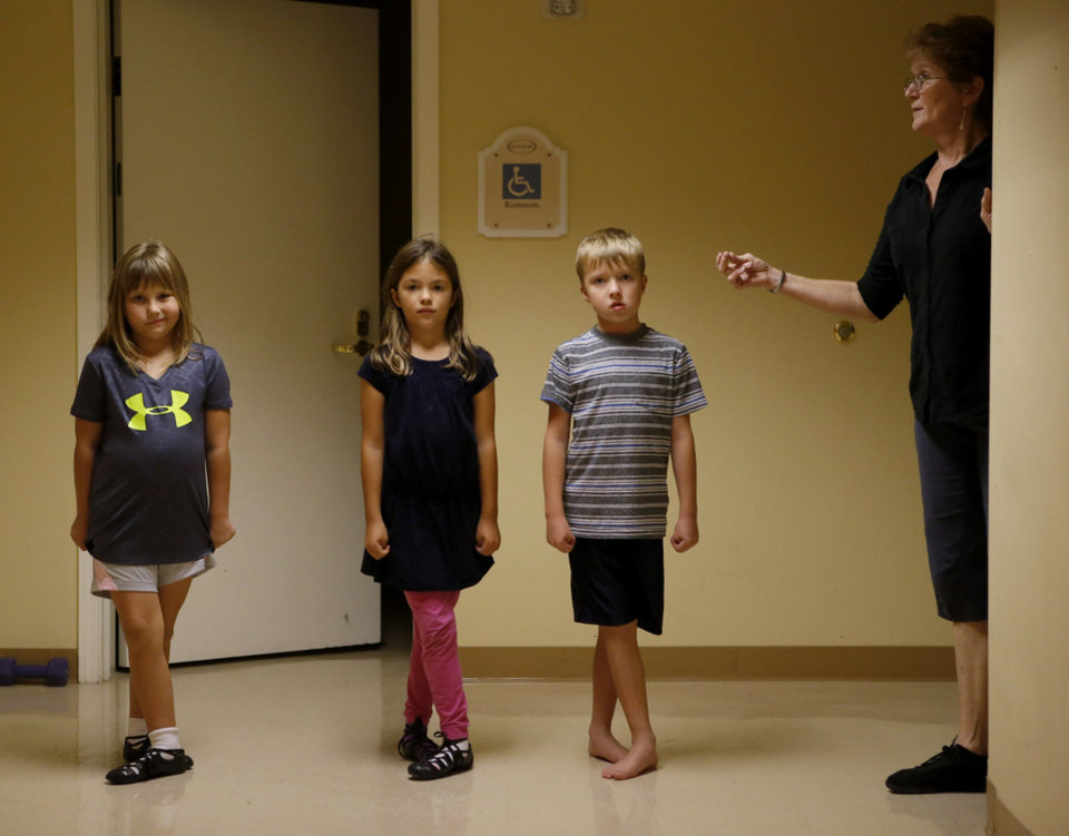Photo -  Eleanor Young, 7, Piper Zuniga, 8, and Evan Goodeon, 7, are taught by Jean Hill during an Irish dance class held at Touchmark Retirement Community in Edmond. [Photo by Bryan Terry, The Oklahoman]