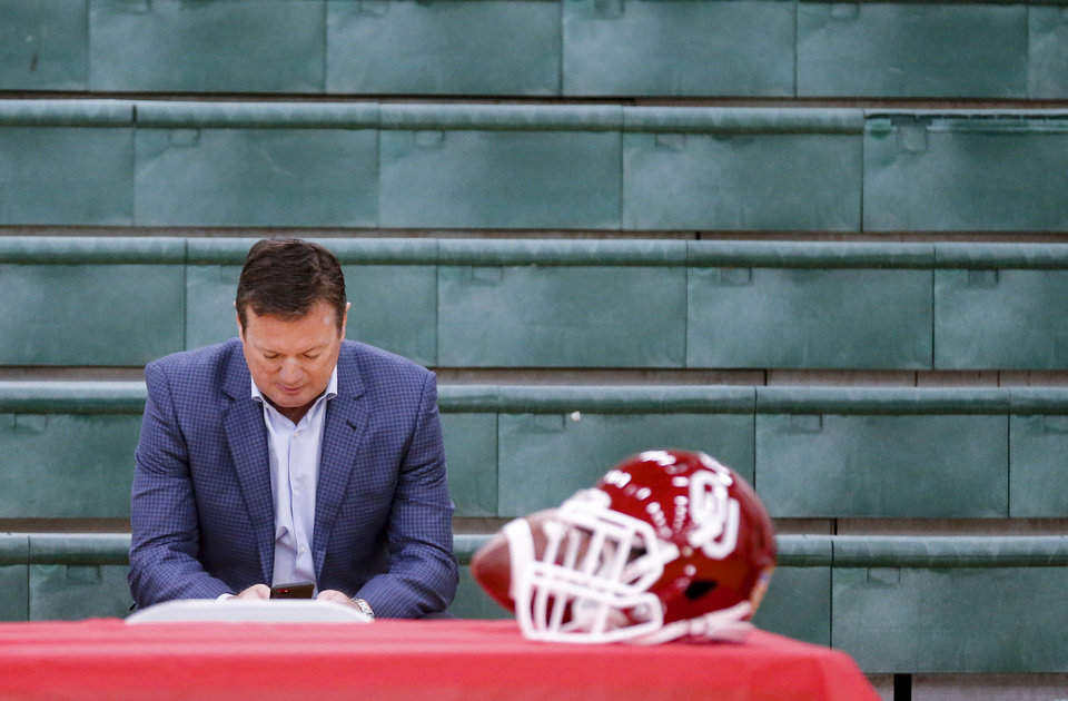 Photo - Former University of Oklahoma football coach Bob Stoops uses his cell phone as he waits for his sons Isaac and Drake Stoops to announce they will be preferred walk-on for OU football during national signing day at Norman North High School in Norman, Okla. on Wednesday, Feb. 7, 2018.  Photo by Chris Landsberger, The Oklahoman