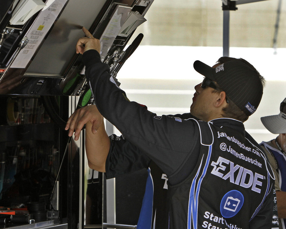 Photo -   No. 31 Chevrolet driver James Buescher checks lap speeds on a monitor in his pit stall with a unidentified crew member after the first practice session for the NASCAR Trucks UNOH 225 auto race at Kentucky Speedway in Sparta, Ky., Thursday, June 28, 2012. (AP Photo/Garry Jones)