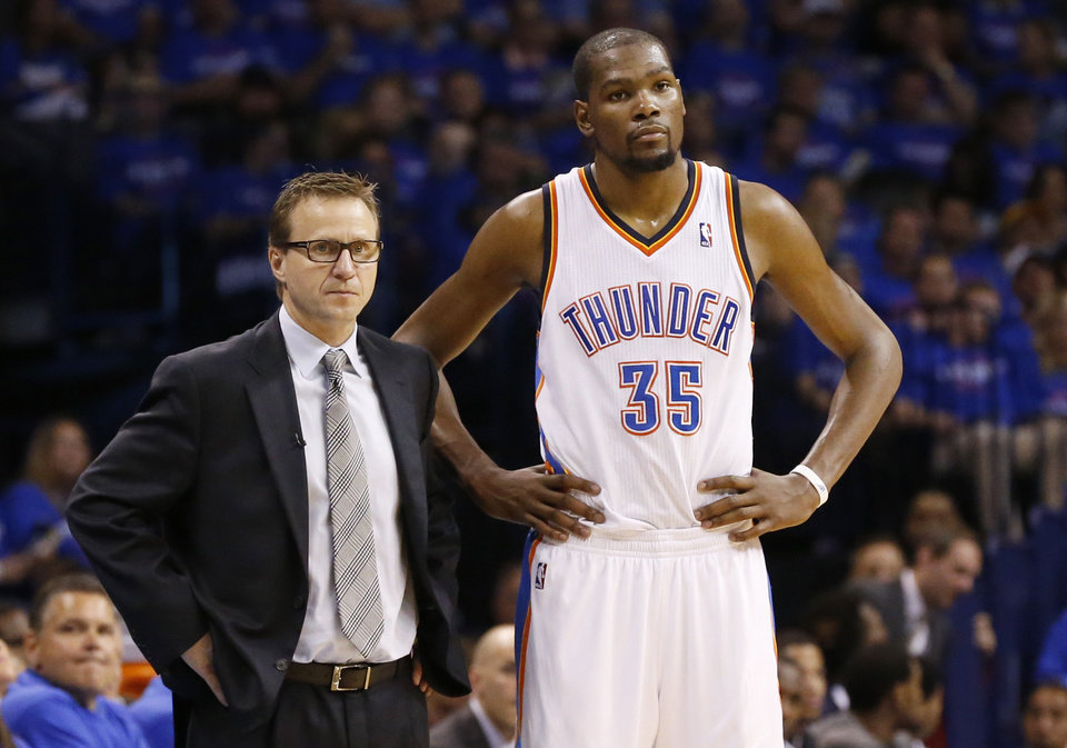 Photo - Oklahoma City Thunder head coach Scott Brooks, left, and forward Kevin Durant, right, watch during a foul shot by the Los Angeles Clippers in the third quarter of Game 1 of the Western Conference semifinal NBA basketball playoff series in Oklahoma City, Monday, May 5, 2014. Los Angeles won 122-105. (AP Photo/Sue Ogrocki)