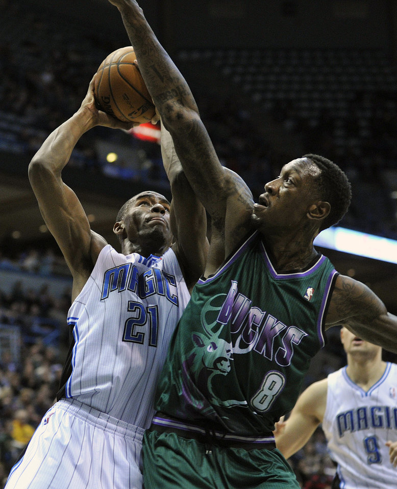 Photo - Orlando Magic's Moe Harkless (21) drives to the basket around Milwaukee Bucks' Larry Sanders (8) during the first half of an NBA basketball game on Saturday, Feb. 2, 2013, in Milwaukee. (AP Photo/Jim Prisching)