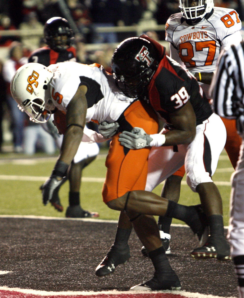 Photo - Keith Totson scores during the first half of the college football game between the Oklahoma State University Cowboys (OSU) and the Texas Tech Red Raiders at Jones AT&T Stadium on Saturday, Nov. 8, 2008, in Lubbock, Tex.  Defending is Marlon Williams.By Steve Sisney/The Oklahoman