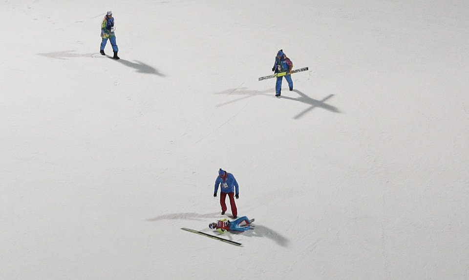 Photo - Russia's Mikhail Maksimochkin lies on the ground after falling during a men's ski jumping large hill training session at the 2014 Winter Olympics, Wednesday, Feb. 12, 2014, in Krasnaya Polyana, Russia. (AP Photo/Matthias Schrader)