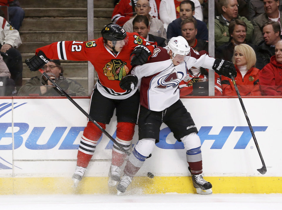 Photo - Chicago Blackhawks center Peter Regin (12) checks Colorado Avalanche defenseman Tyson Barrie (4) along the boards during the first period of an NHL hockey game Tuesday, March 4, 2014, in Chicago. (AP Photo/Charles Rex Arbogast)