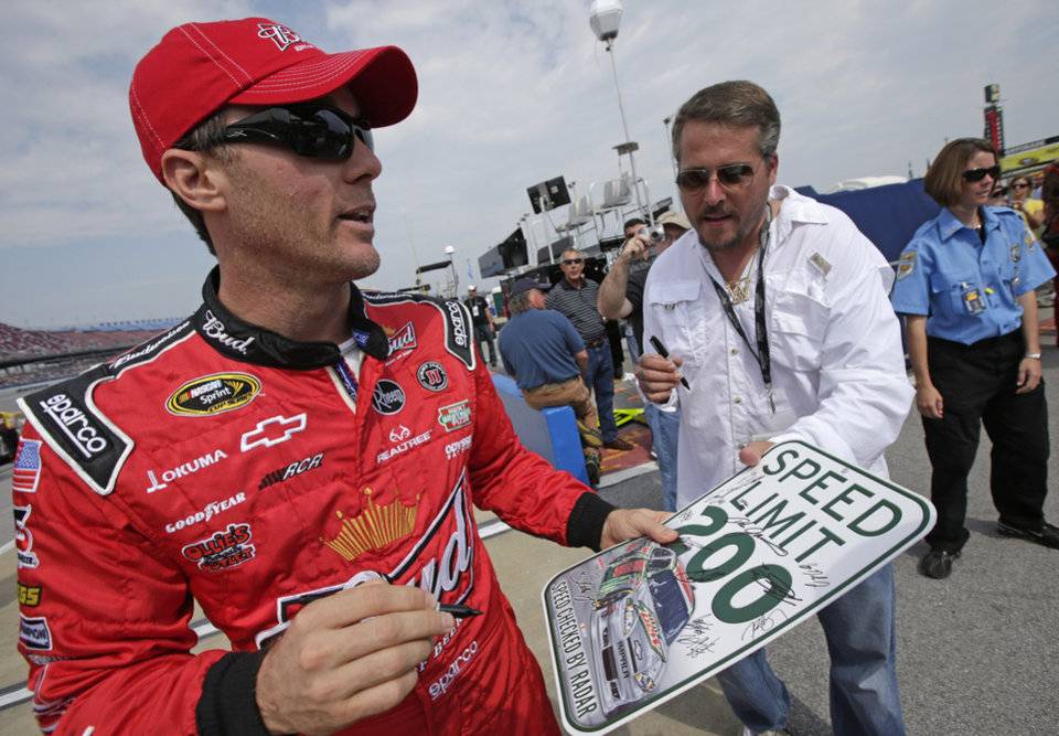 Photo -   NASCAR driver Kevin Harvick signs autographs for fans prior to qualifying at the Talladega Superspeedway in Talladega, Ala., Saturday, Oct. 6, 2012. The drivers were qualifying for the Sunday running of the NASCAR Sprint Cup Series auto race. (AP Photo/Dave Martin)