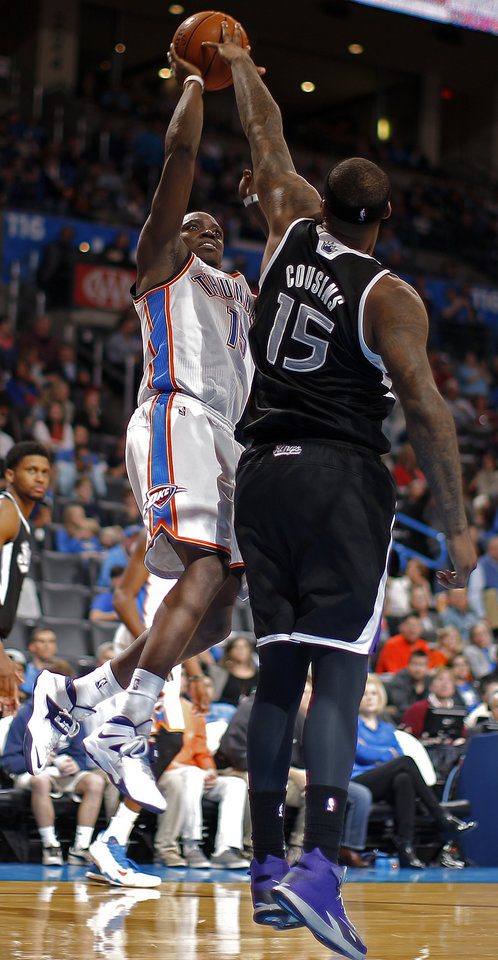 Photo - Oklahoma City's Reggie Jackson (15) shoots as Sacramento's DeMarcus Cousins (15) defends during the NBA game between the Oklahoma City Thunder and the Sacramento Kings at the Chesapeake Energy Arena, Sunday, Jan. 19, 2014.  Photo by Sarah Phipps, The Oklahoman
