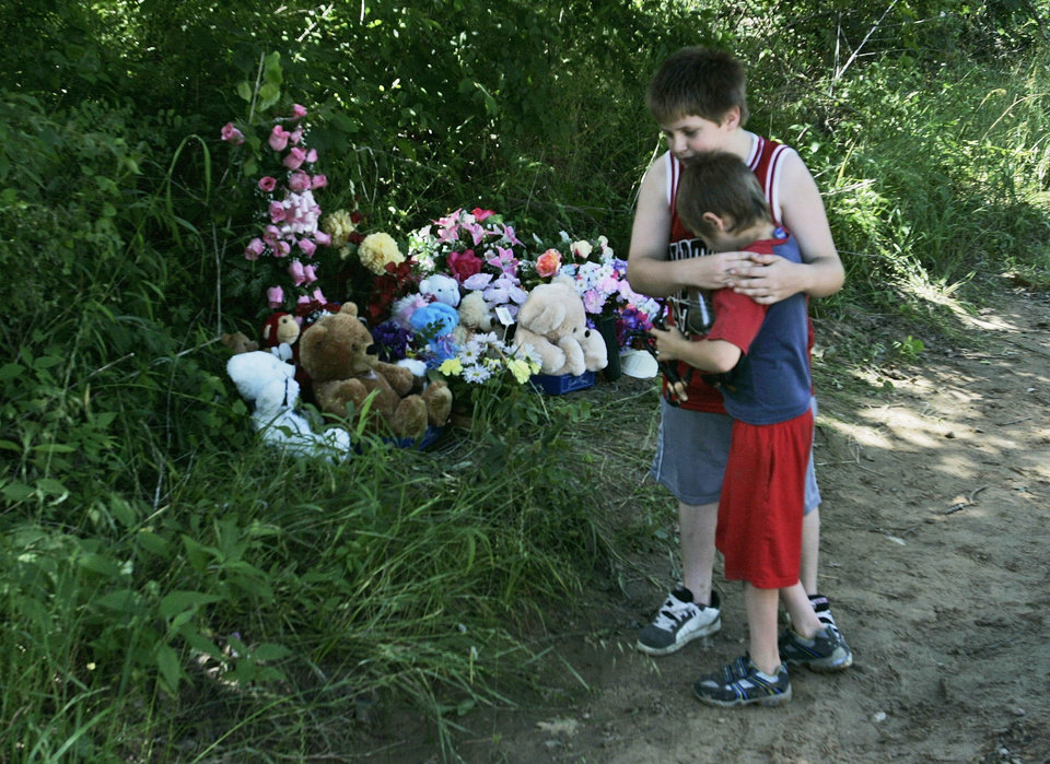 Photo - Dakota Padgett, 10, hugs his brother, Devon Padgett, 7, in front of a memorial on the side of the road for Skyla Whitaker, 11, and Taylor Paschal-Placker, 13, on Wednesday, June 11, 2008. The two girls were found murdered Sunday night. (AP Photo)