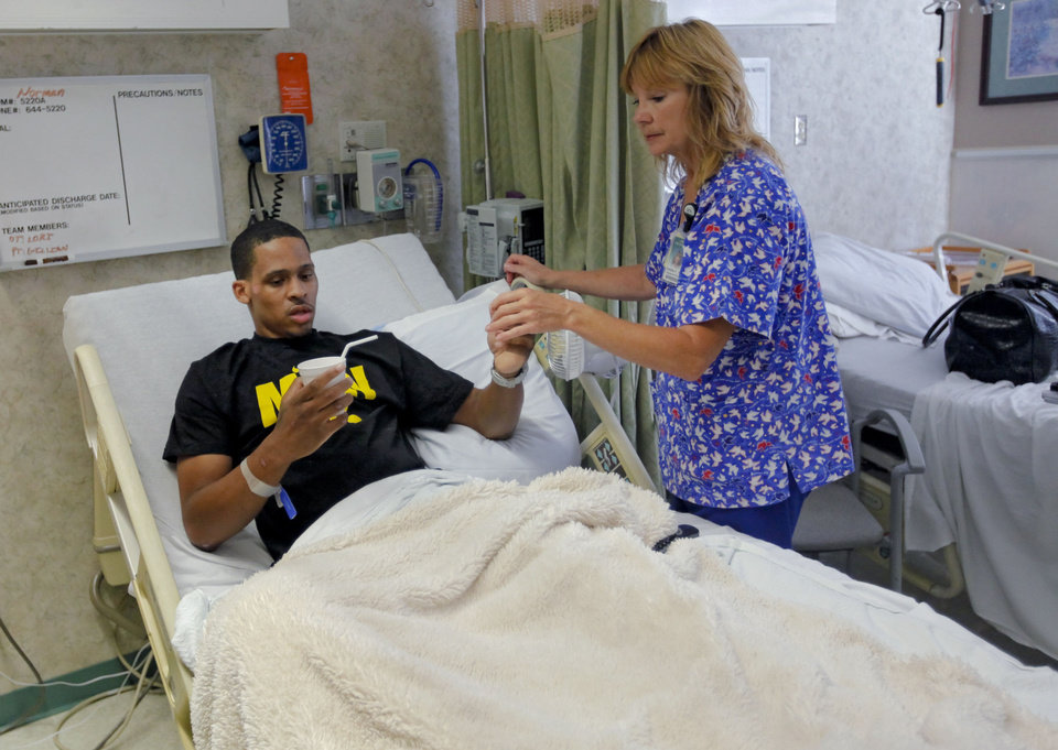 Photo - Bricktown shooting victim Norman Richards, 22, is given medicine by Debbie Foyil, RN, as he awaits discharge from Jim Thorpe Rehabilitation Hospital on Friday, June 22, 2012.  Photo by Chris Landsberger, The Oklahoman  CHRIS LANDSBERGER - CHRIS LANDSBERGER