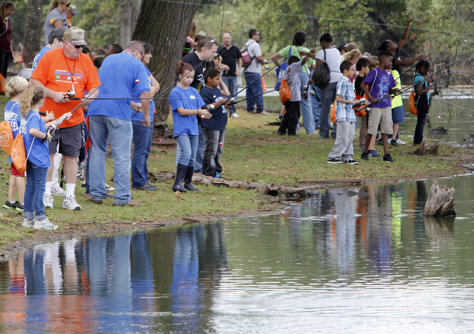 Photo - School children do some fishing during school day of the Oklahoma Wildlife Expo at the Lazy E Arena and Ranch in Guthrie, OK, Friday, September 28, 2012,  By Paul Hellstern, The Oklahoman
