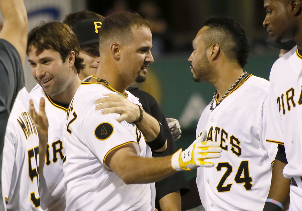 Photo - Pittsburgh Pirates' Gaby Sanchez, center, is greeted by teammates Neil Walker, left, and Pedro Alvarez, right, after driving in the game winning run with a sacrifice fly in the bottom of the ninth inning of the baseball game against the Atlanta Braves on Wednesday, Aug. 20, 2014, in Pittsburgh. The Pirates won 3-2. (AP Photo/Keith Srakocic)