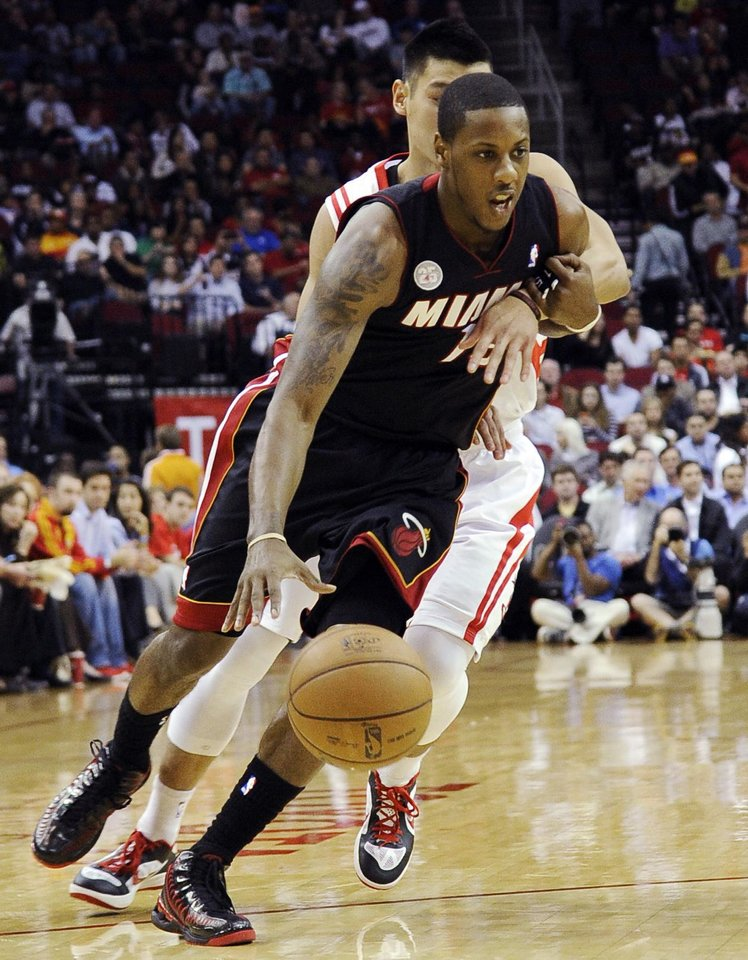 Photo -   Miami Heat's Mario Chalmers, front, is wrapped up by Houston Rockets' Jeremy Lin in the first half of an NBA basketball game, Monday, Nov. 12, 2012, in Houston. (AP Photo/Pat Sullivan)