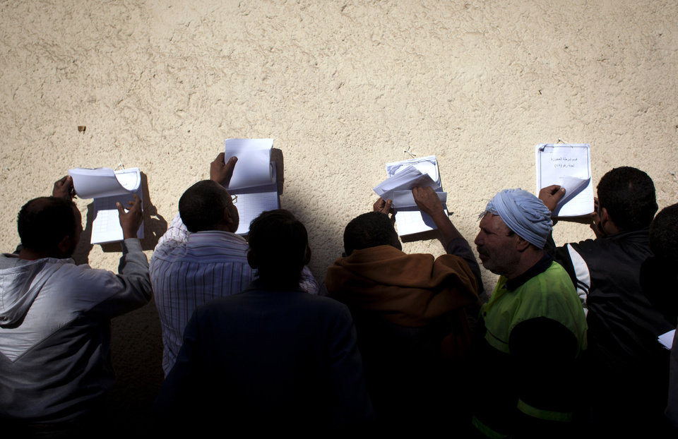 Photo - Egyptian voters check voter lists outside a polling station during the second round of a referendum on a disputed constitution drafted by Islamist supporters of president Mohammed Morsi, in Giza, Egypt, Saturday, Dec. 22, 2012. (AP Photo/Nasser Nasser)
