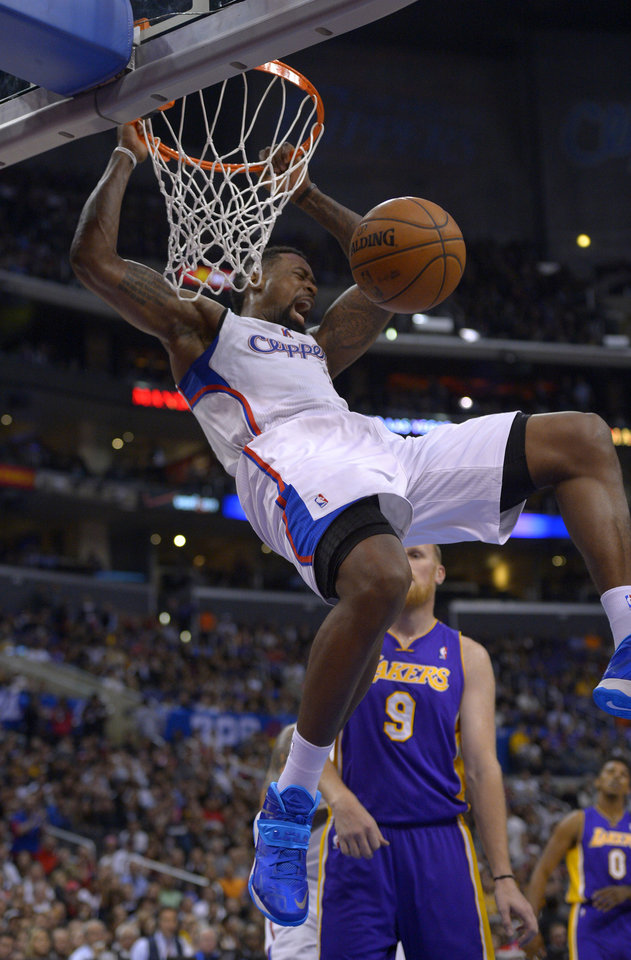 Photo - Los Angeles Clippers forward Jared Dudley, top, dunks as Los Angeles Lakers center Chris Kaman looks on during the first half of an NBA basketball game, Friday, Jan. 10, 2014, in Los Angeles. (AP Photo/Mark J. Terrill)