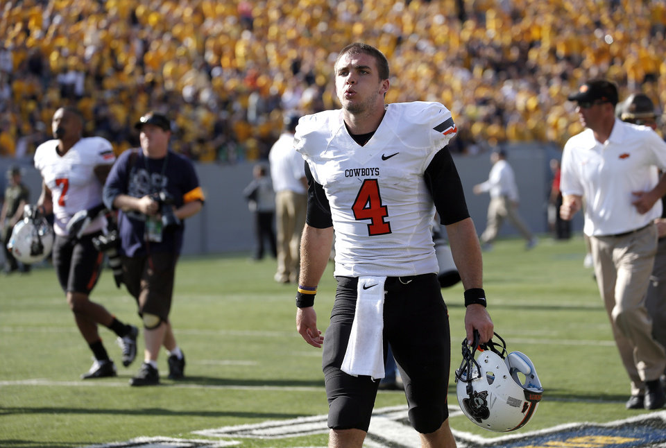 Oklahoma State's J.W. Walsh (4) walks off the field after the Cowboys loss West Virginia University on Mountaineer Field at Milan Puskar Stadium in Morgantown, W. Va.,   Saturday, Sept. 28, 2013. Photo by Sarah Phipps, The Oklahoman