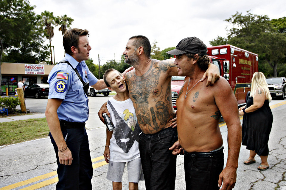 Photo -   Pinellas Park Paramedic Ryan Mitchell, left, talks to Darrell Edgar, 46, center, as he limps away from the scene where Anthony Giancola, 45, crashed his car in Lealman, Fla., Friday, June 22, 2012. Authorities said Giancola, an ex-Tampa Bay-area middle school principal who lost his job over a drug arrest five years ago, went on a rampage Friday, stabbing several people, killing at least two. Authorities said there were 11 victims in all, and several are being treated at area hospitals for injuries ranging from minor to life-threatening. (AP Photo/Tampa Bay Times, Melissa Lyttle) TAMPA OUT; CITRUS COUNTY OUT; PORT CHARLOTTE OUT; BROOKSVILLE HERNANDO TODAY OUT