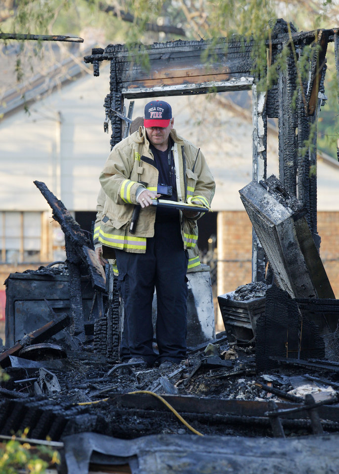 Photo -  An Oklahoma City firefighter looks through the damage after an explosion cause a fatal house fire at 1310 SW 23 in Oklahoma City. Photo by Paul B. Southerland, The Oklahoman   PAUL B. SOUTHERLAND -