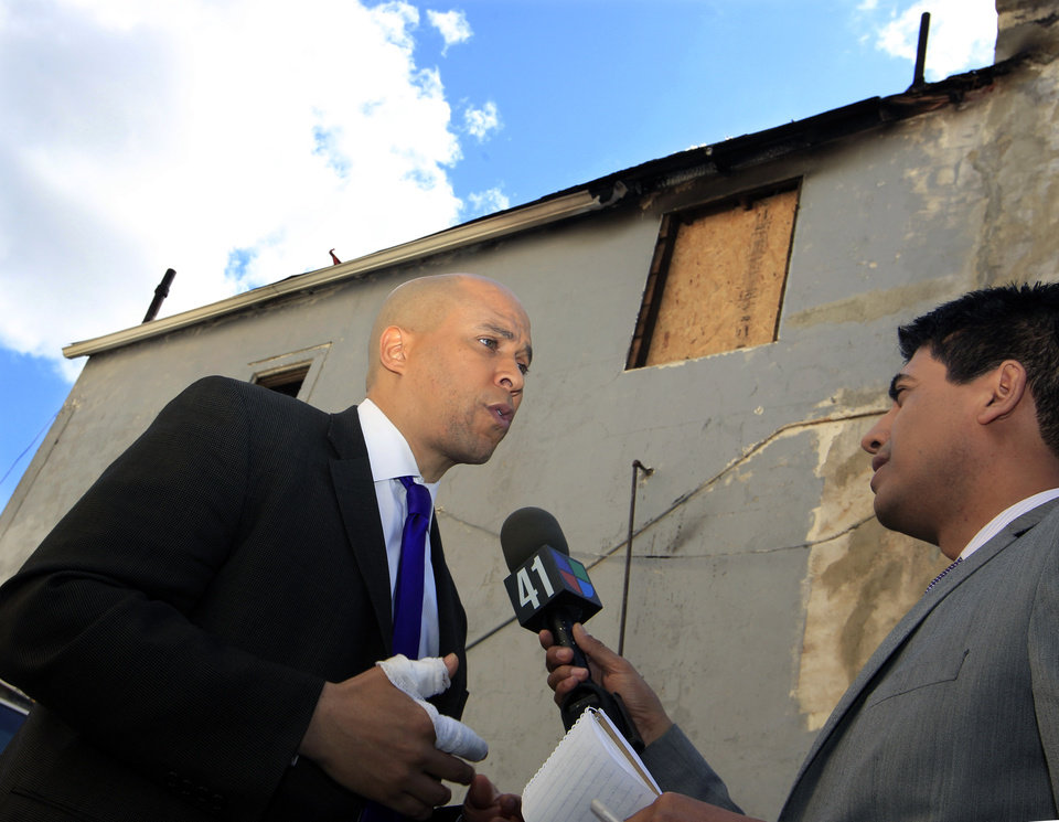 Photo -   Newark Mayor Cory Booker has a bandaged right hand as he answers a question next to a burned home in Newark, N.J., Friday, April 13, 2012, where he was credited with rescuing a neighbor Thursday from a fire. Booker said Friday he feared for his life as he helped rescue a neighbor from a fire before firefighters arrived. He described how he returned home Thursday night and saw his neighbor's home engulfed in flames. The woman Booker helped save is in stable condition. (AP Photo/Mel Evans)