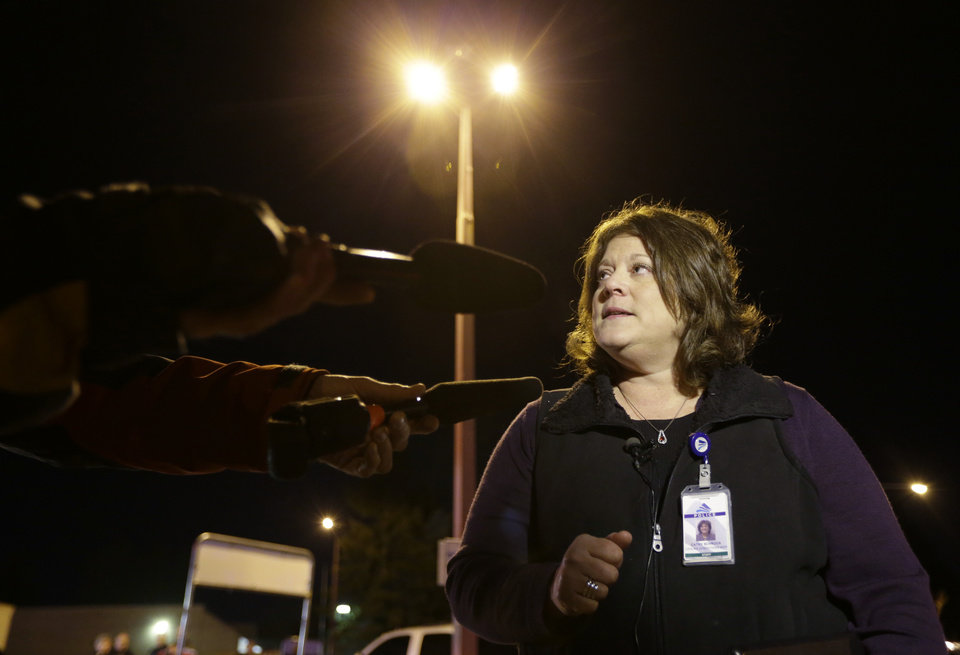 Photo - Federal Way Police spokeswoman Cathy Schrock talks to reporters about an overnight shooting that she said left five people dead, Monday, April 22, 2013, at an apartment complex in Federal Way, Wash. (AP Photo/Ted S. Warren)