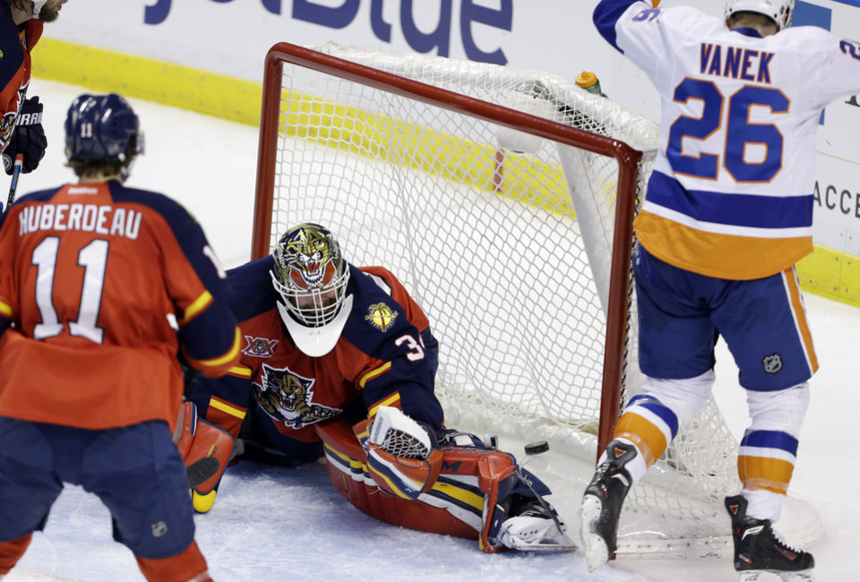 Photo - The puck gets past Florida Panthers goalie Tim Thomas (34) on a goal scored by New York Islanders' Thomas Vanek (26) during the third period of an NHL hockey game, Tuesday, Jan. 14, 2014, in Sunrise, Fla. The Panthers defeated the Islanders 4-2. (AP Photo/Lynne Sladky)