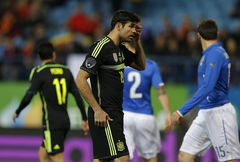 Photo - Spain's Diego Costa, centre touches his head during a friendly soccer match against Italy at the Vicente Calderon stadium in Madrid, Wednesday March 5, 2014. (AP Photo/Paul White)
