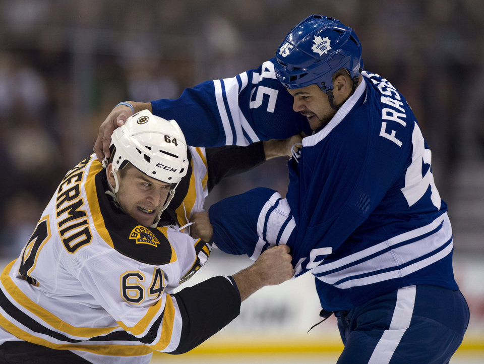 Toronto Maple Leafs defenseman Mark Fraser, right, and Boston Bruins left winger Lane MacDermid exchange blows during a fight in the first period of an NHL hockey game in Toronto on Saturday, Feb. 2, 2013. (AP Photo/The Canadian Press, Frank Gunn)