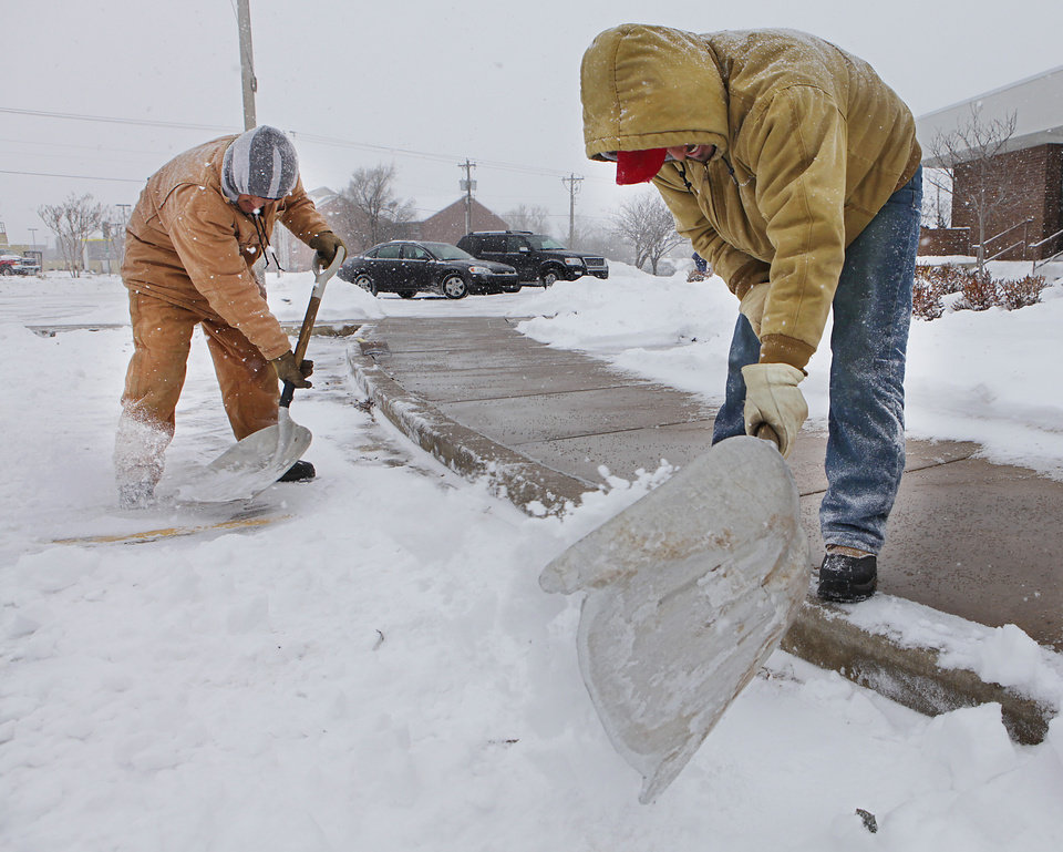 Photo - Workers clear the sidewalks and parking lot of thew Kirkpatrick Bank in Edmond, Wednesday, February 9 , 2011. Photo by David McDaniel, The Oklahoman