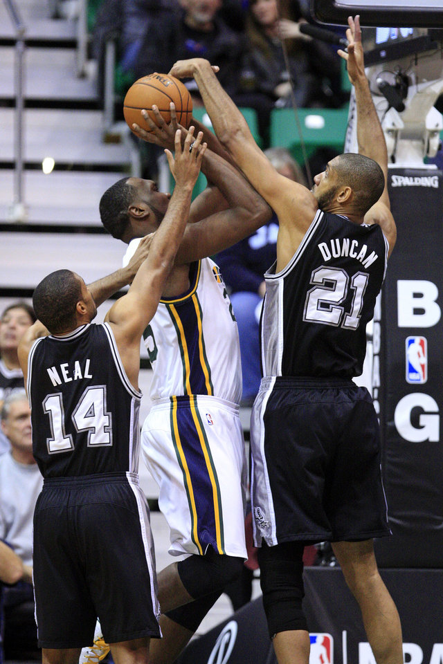 San Antonio Spurs forward Tim Duncan (21) and guard Gary Neal (14) defend against Utah Jazz center Al Jefferson (25) in the first quarter during an NBA basketball game, Wednesday, Dec. 12, 2012, in Salt Lake City. (AP Photo/Rick Bowmer)