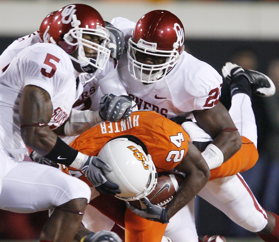 Photo - Sooners wrangle OSU's Kendall Hunter to the ground during the first half of the college football game between the University of Oklahoma Sooners (OU) and Oklahoma State University Cowboys (OSU) at Boone Pickens Stadium on Saturday, Nov. 29, 2008, in Stillwater, Okla. STAFF PHOTO BY BRYAN TERRY