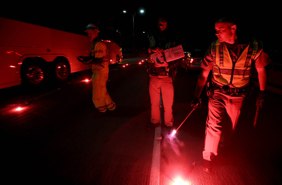 Photo - California Highway Patrolmen light flares as they investigate the scene of a limousine fire on the westbound side of the San Mateo-Hayward Bridge in Foster City, Calif., on Saturday, May 4, 2013. Five people died when they were trapped in the limo that caught fire as they were traveling, and four others and the driver were able to escape, according to the Oakland Tribune-Bay Area News Group. (AP Photo/Oakland Tribune-Bay Area News Group, Jane Tyska)