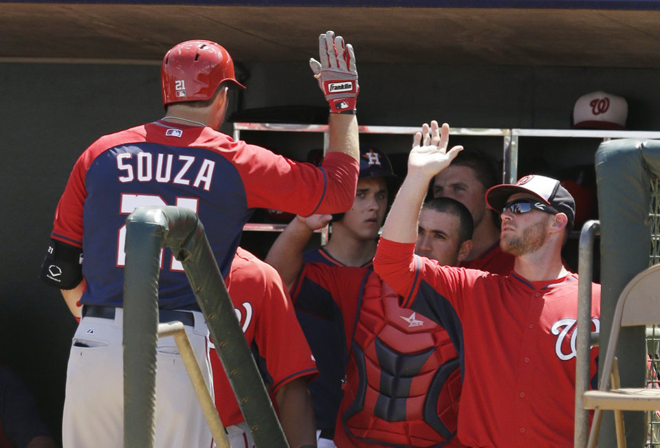 Photo - Washington Nationals' Steven Souza, left, is congratulated in the dugout after his second home run of the game during the fourth inning of a spring exhibition baseball game against the Houston Astros in Kissimmee, Fla., Sunday, March 16, 2014. (AP Photo/Carlos Osorio)