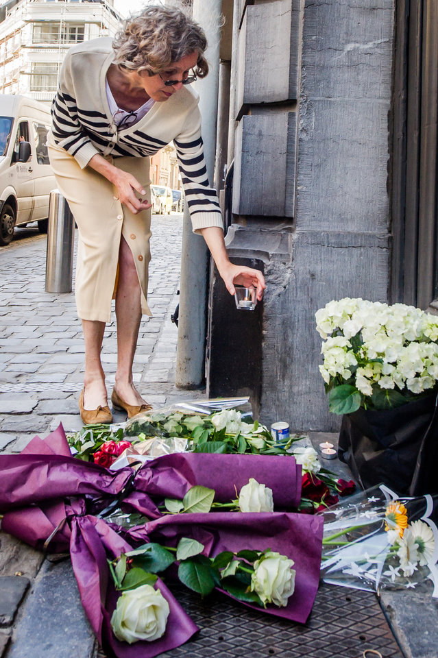 Photo - A woman places a candle next to flowers at the Jewish Museum in Brussels, Sunday May 25, 2014.  Police stepped up security at Jewish institutions, schools and synagogues after three people were killed and one seriously injured in a spree of gunfire at the Jewish Museum in Brussels on Saturday. (AP Photo/Geert Vanden Wijngaert)