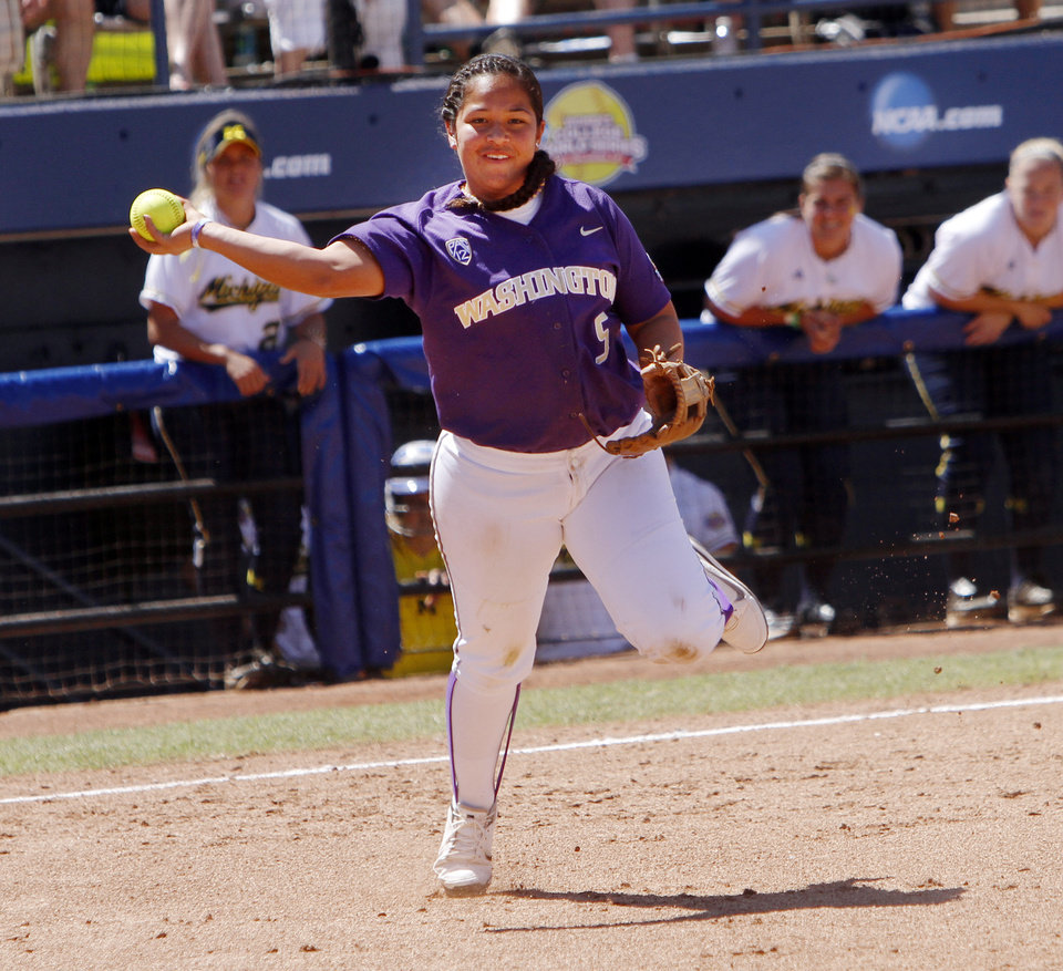 Photo - Washington Huskies third baseman Kimberlee Souza throws to first base in the Women's College World Series elimination game versus Michigan. The Washington Huskies would won 4-1 on June 2, 2013. Photo by KT KING, The Oklahoman