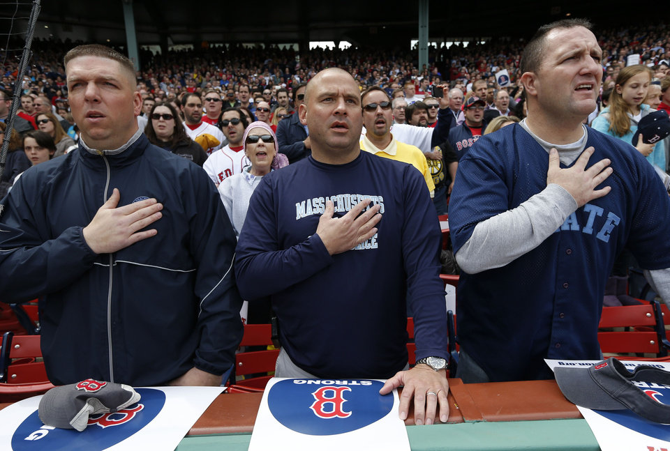 Three members of the Massachusetts State Police place their hands over their heart during the national anthem before a baseball game between the Boston Red Sox and the Kansas City Royals in Boston, Saturday, April 20, 2013. (AP Photo/Michael Dwyer) ORG XMIT: MAMD140