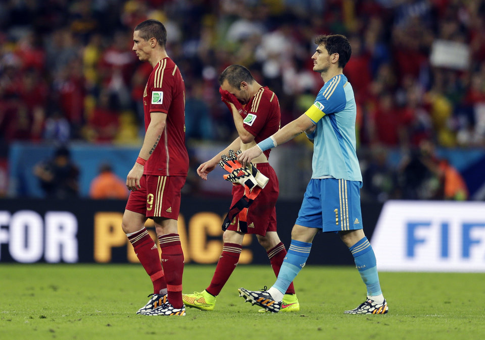 Photo - From left, Spain's Fernando Torres, Andres Iniesta and goalkeeper Iker Casillas walk off the pitch following their group B World Cup soccer match between Spain and Chile at the Maracana Stadium in Rio de Janeiro, Brazil, Wednesday, June 18, 2014. Defending champion Spain was eliminated from the World Cup after losing to Chile 2-0.  (AP Photo/Natacha Pisarenko)