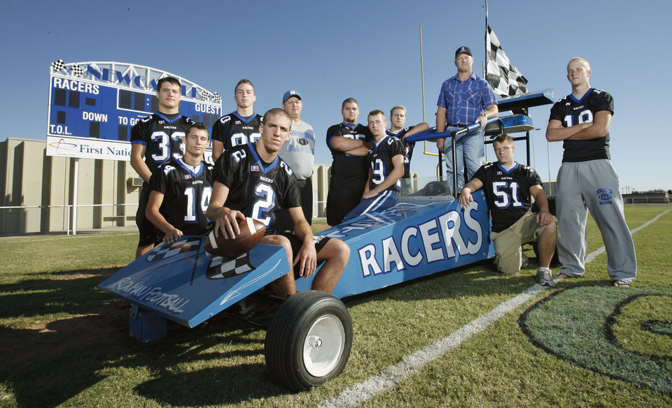 HIGH SCHOOL FOOTBALL: Newcastle players and coach Rocky Guerra (33) Brandon Buie (14), Robert Wilder (30), Trevor Evans (2), head coach Keith Bolles, Matt Enarson (75), Gerald Smith (29), Ryan Gotte (24), driver Jim Ogle, Garret Romesburg (51) and Jeremy Hey (18) gather around the team mascot named