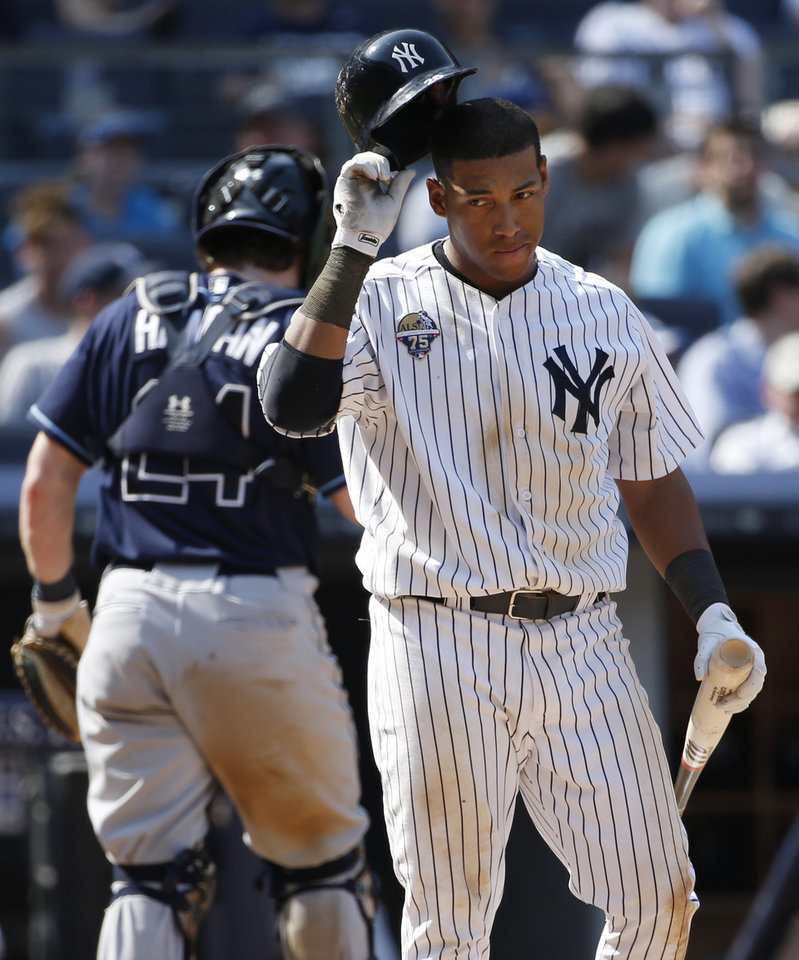 Photo - FILE - In this July 2, 2014, file photo, New York Yankees Yangervis Solarte removes his batting helmet after striking out with a runner on second in the eight inning of a baseball game against the Tampa Bay Rays at Yankee Stadium in New York. Trying to add offense at third base, the Yankees have acquired Chase Headley from the San Diego Padres on Tuesday, July 22, 2014, for infielder Yangervis Solarte and right-hander Rafael De Paula. (AP Photo/Kathy Willens, File)