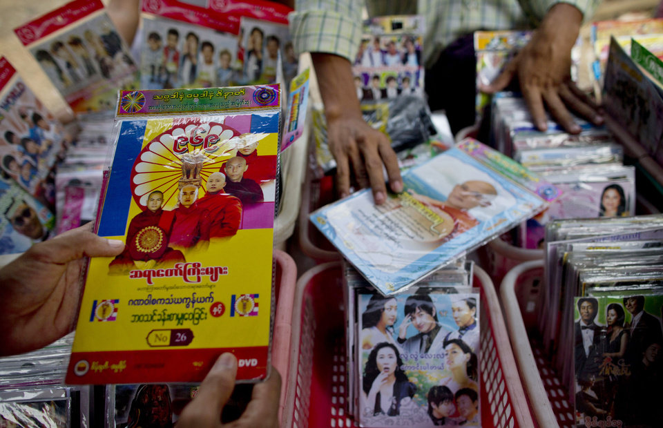 Photo - In this April 4, 2013 photo, a man holds a DVD with sermons of Buddhist monks promoting the 969 movement at a DVD shop in the Kyimyindaing market in Yangon, Myanmar.  Buddhist monk Wirathu says,