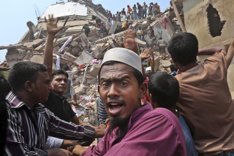 Photo - Bangladeshi rescue workers work at the site of a building that collapsed Wednesday in Savar, near Dhaka, Bangladesh, Friday, April 26, 2013. The death toll reached hundreds of people as rescuers continued to search for injured and missing, after a huge section of an eight-story building that housed several garment factories splintered into a pile of concrete.(AP Photo/Kevin Frayer)