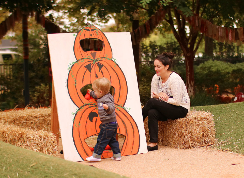 Photo -  Sarah Singleton watches her friend Katie Hurst's son, Elias Hurst, 1, toss bean bags into a pumpkin board game. [Photo by Doug Hoke, The Oklahoman]