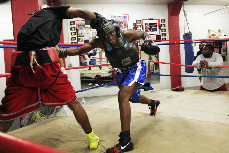 Photo -   In this Sept. 18, 2012, photo, Olympic gold medal boxer Claressa Shields spars with training partner Ardreal Holmes at the Berston Field House in Flint, Mich. Unwilling to accept a life of poverty, crime or worse, Shields found her family, her passion and her way out through a small, dark basement gym. (AP Photo/Carlos Osorio)