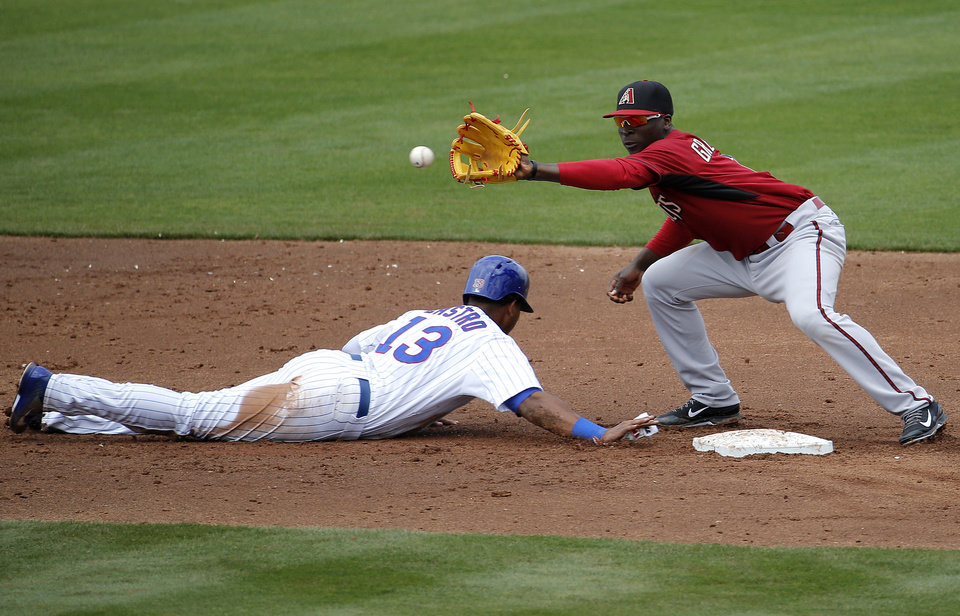 Photo - Arizona Diamondbacks' Didi Gregorius waits for a pick-off throw as Chicago Cubs' Starlin Castro dives back to second during the second inning of a spring training baseball game, Thursday, Feb. 27, 2014, in Mesa, Ariz. (AP Photo/Matt York)