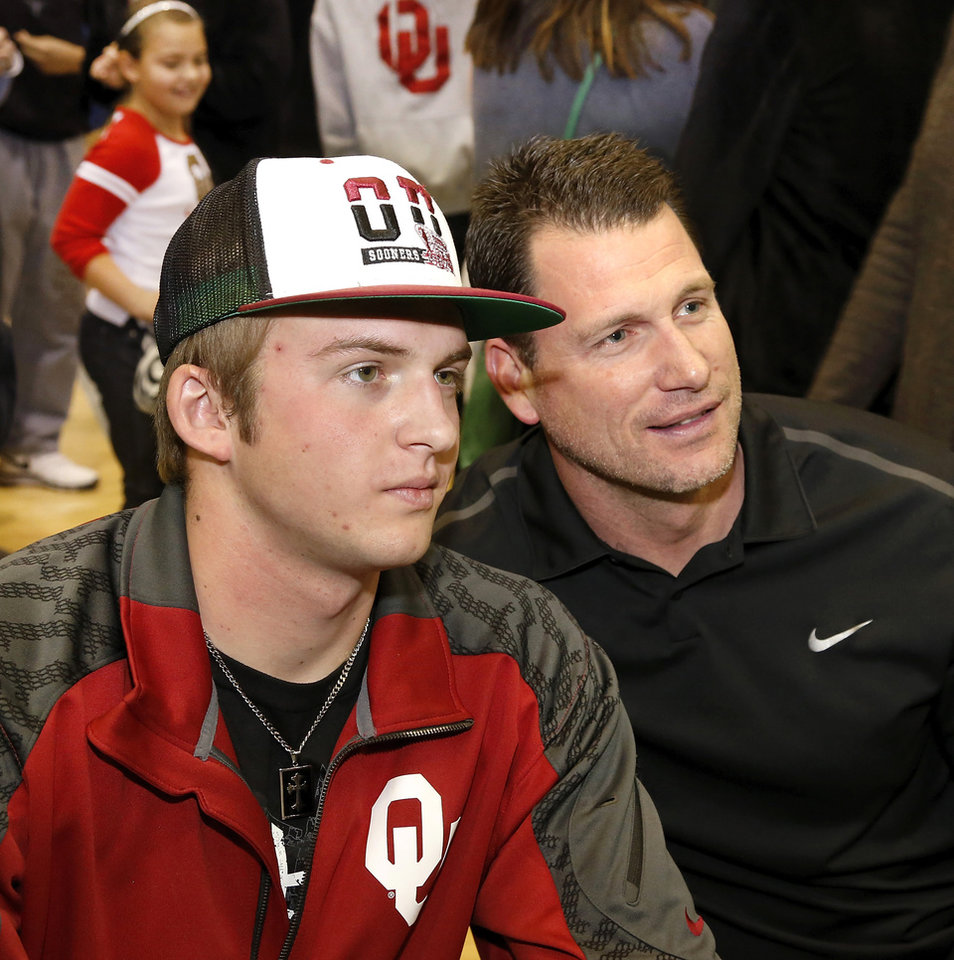 Photo - Justice Hansen poses for a photo with his dad, Dusty, who plated baseball for the Sooners. Justice Hansen is an Edmond Santa Fe quarterback who signed a letter of intent to play football with OU during signing day ceremony in the gymnasium at Edmond Santa Fe High School on Wednesday, Feb. 5, 2014.   Photo by Jim Beckel, The Oklahoman