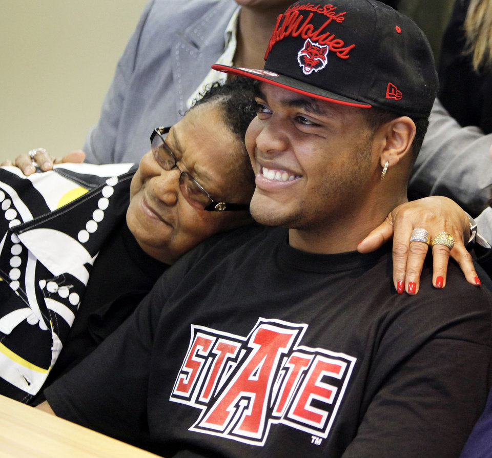 Photo - Loyce Dean, left, puts her arm around her grandson Quintaz Struble as they pose for a family photo during the National Signing Day ceremony at Heritage Hall in Oklahoma City, Wednesday, Feb. 1, 2012. Loyce Dean is the mother of former Millwood athletic standout Mandrell Dean, Quintaz Struble's father. Struble signed to play football at Arkansas State. Photo by Nate Billings, The Oklahoman