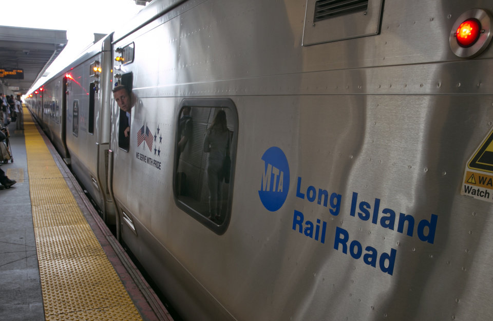 Photo - A conductor checks the platform from his train at the Jamaica station of the Long Island Rail Road, in the Queens borough of New York, Wednesday, July 16, 2014. Negotiations aimed at avoiding a walkout at the nation's largest commuter railroad resumed Wednesday after Gov. Andrew Cuomo prodded both sides to find an agreement that would keep 300,000 daily riders from being forced to find alternate ways of getting in and out of New York City. (AP Photo/Richard Drew)