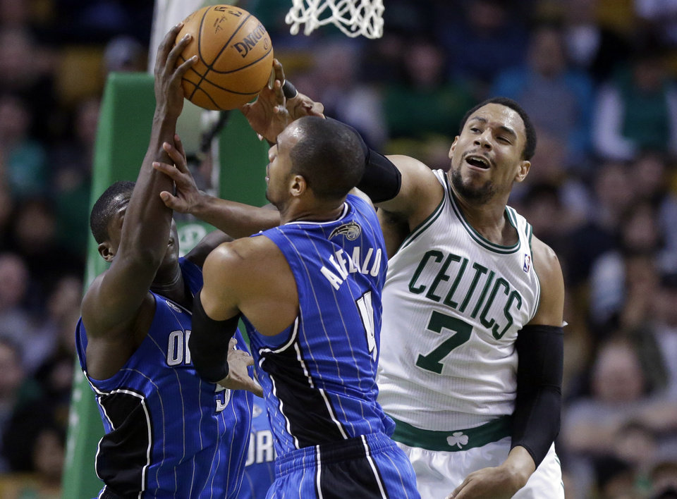 Photo - Boston Celtics center Jared Sullinger (7) grapples with Orlando Magic guard Victor Oladipo, behind left, and guard Arron Afflalo, center, for control of the ball in the third quarter of an NBA basketball game on Sunday, Feb. 2, 2014, in Boston. The Celtics won 96-89. (AP Photo/Steven Senne)